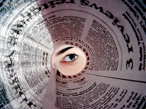 Menina olhando dentro de um jornal / Crédito:SXC.hu